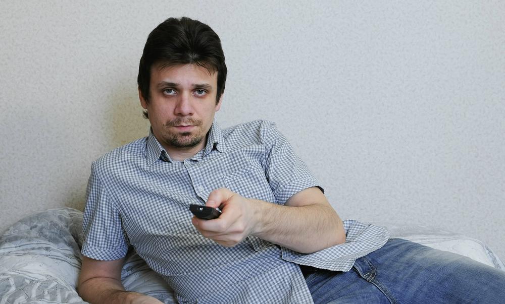 мужчина на диване переключает каналы ТВ