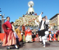 Люди в народных костюмах возлагают к ногам статуи Девы Марии корзины с цветами и плодами (www.turispain.com)
